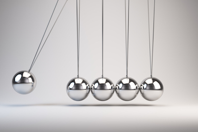 Newton's cradle perpetual motion on office desk