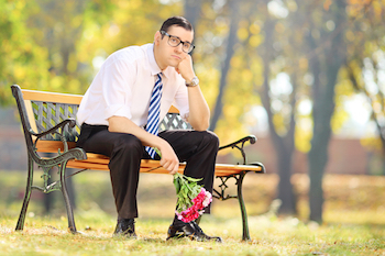 Man on bench dealing with disappointment and emotional reactions at work