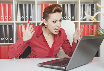 Woman upset with computer and dealing with negative emotional reactions at work